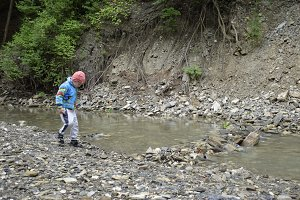 A child near a mountain stream. The boy walks along the creek.
