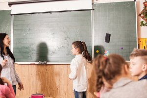 Teacher helping pupil at blackboard