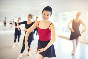 Asian adult woman smiling while performing ballet in class