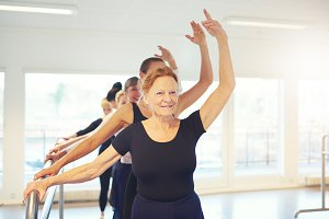 Smiling aged woman dancing ballet in group