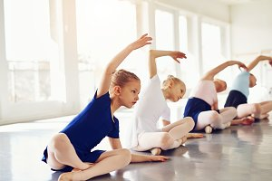 Little girls stretching on floor in ballet class
