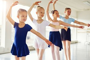 Group of cute girls standing and practicing ballet