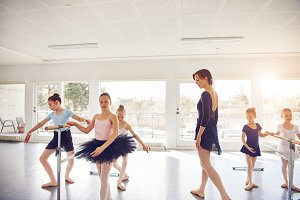 Little sporty girls performing ballet in class
