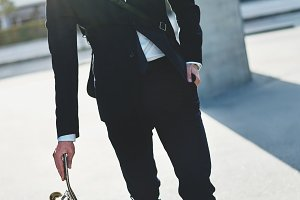 Confident handsome man wearing suit with skateboard