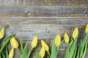 Yellow tulips on rustic wood table