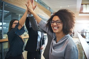 Smiling black businesswoman giving high five to ofiice team