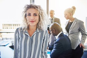 Young businesswoman smiling with colleagues working in the background