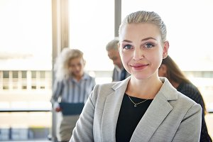 Confident young businesswoman smiling with coworkers talking in the background
