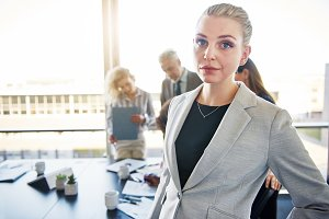 Confident young businesswoman with coworkers talking in the background