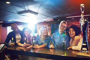 Cheerful people with beer at bar counter