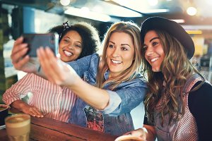 Happy young women friends posing for a selfie
