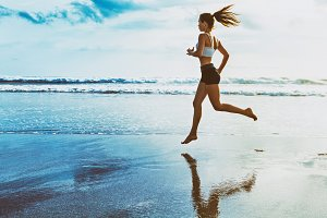 Girl running along sea surf