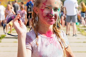 Joyful girl sprinkled with dry paint