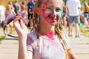 Joyful girl sprinkled with dry paint