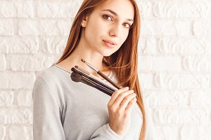Beautiful young woman with nude face makeup with brushes for makeup