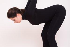 Beautiful athletic girl in black suit doing yoga asanas. Isolated on white background.