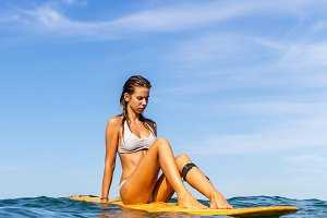 Beautiful girl with surf in ocean.