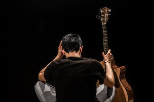 young man with acoustic guitar on black background