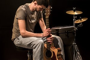 musician plays acoustic guitar and percussion instruments, black background