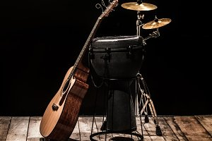 percussion instruments with an acoustic guitar on wooden boards with a black background