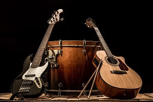 musical instruments, bass drum barrel acoustic guitar and bass guitar on a black background