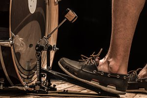 percussion instrument, bass drum with pedal on wooden Board with black background, men's foot