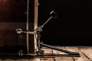 percussion instrument, bass drum with pedal on wooden boards with a black background