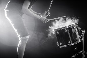 man plays musical percussion instrument with sticks, a musical concept, beautiful lighting on the stage