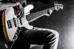 the man plays bass guitar on a black background, the music conce