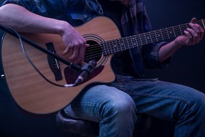 man playing acoustic guitar on a black background, the music concept, beautiful lighting on the stage