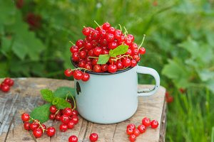 Metal mug with red currant on the table, soft focus background