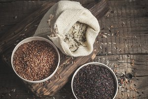 Selection of red, black and mixed rice on an old wooden background.Top view with copy space
