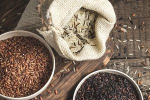 Selection of red, black and mixed rice on an old wooden background