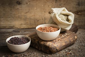 Set of red, black and mixed rice on an old wooden background