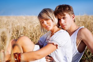 young man and woman on wheat field