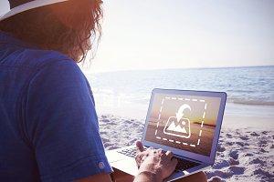 Man Using Laptop On Beach Mockup