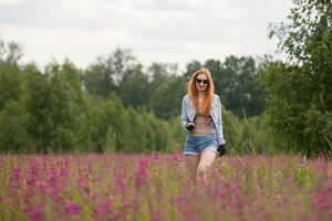 Beautiful red-haired girl walking on a flower meadow