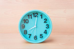 green clock on wood background