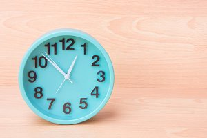 Green clock timer on wood background