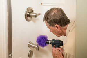 Senior man cleaning a shower with power drill