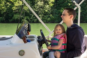 Young baby girl or toddler driving speed boat with father