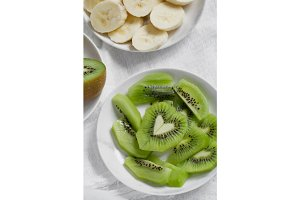 Top view of pieces of fresh banana and kiwi in the shape of a heart on a white plate. Healthy eating concept.