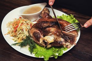 Man eats tasty dish of pork shank