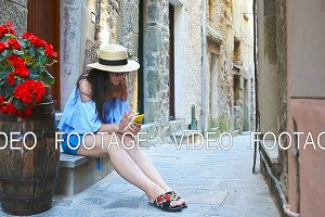 Beautiful happy woman on european vacation in Cinque Terre. Young caucasian tourist taking selfie at the old street