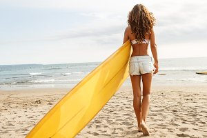Beautiful girl with surf on beach.