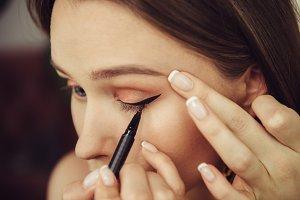 Woman painting black makeup arrows