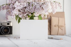 Blank white greeting card with lilac flowers bouquet and envelope with vintage camera on white wooden background. mock up