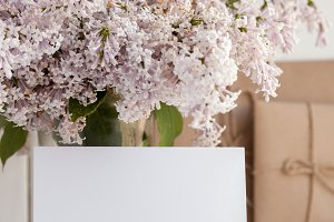 Blank white greeting card with lilac flowers bouquet and envelope on white wooden background. mock up