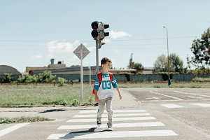 Schoolboy crossing a road