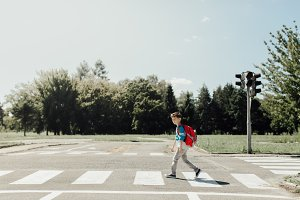 Schoolboy crossing a road